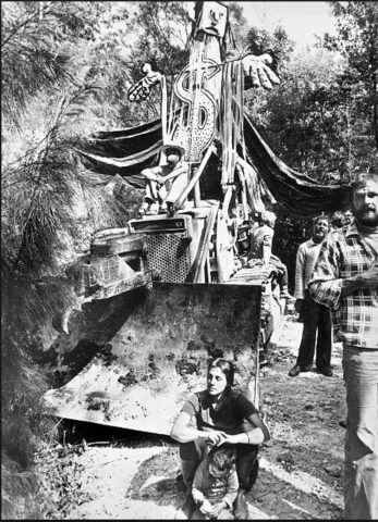 A decorated bulldozer at Terania Creek in 1979 with protesters sitting on top and in front of it.